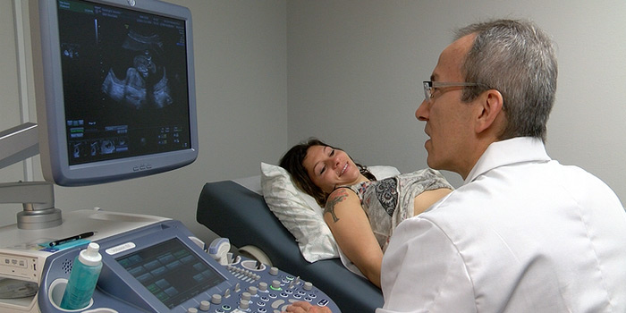 Dr Luis Tobon using ultrasound of woman.